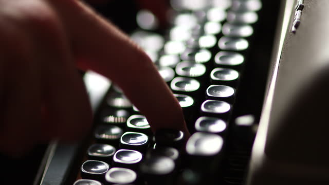 Handheld close up shot of fingers typing on a mechanical typewriter