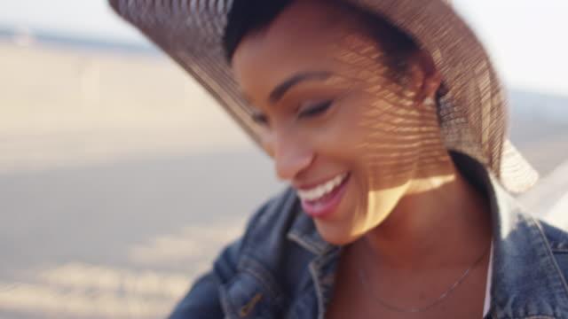 vídeos de stock, filmes e b-roll de handheld close up shot of pretty black woman at the beach talking to friend - chapéu de sol