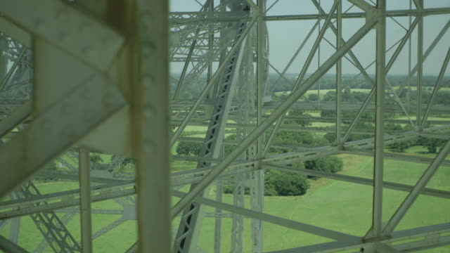 Handheld close-up focus pull between steel beams holding up the Lovell Telescope at the Jodrell Bank Observatory in Cheshire, UK.
