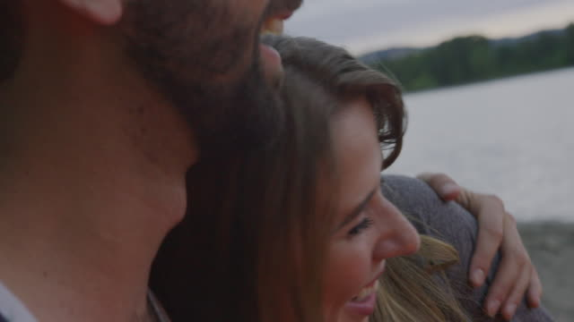 handheld close-up of happy couple talking while relaxing at campsite during sunset - young men stock videos & royalty-free footage