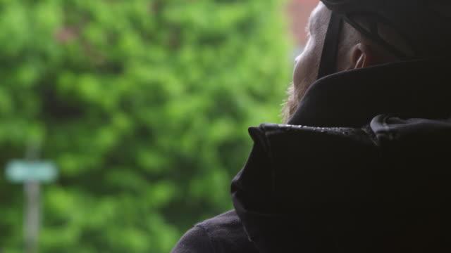 handheld close-up of male commuter wearing bicycle helmet looking away - cycling helmet stock videos & royalty-free footage