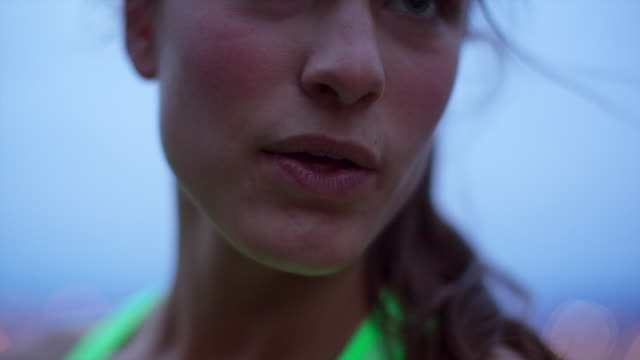 handheld close-up of tired female athlete smiling against sky at dusk - tired stock videos & royalty-free footage