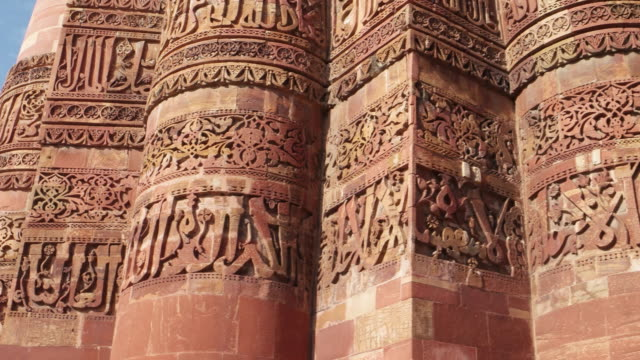 a handheld close-up pov of the qutb minar and it's engravings and architecture, stabilized with a handheld 3 way gimbal - minareto video stock e b–roll