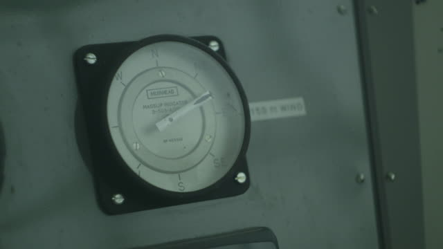 Handheld close-up sequence showing a 20th Century analogue meter resembling a compass displaying [northeasterly] wind direction, UK.