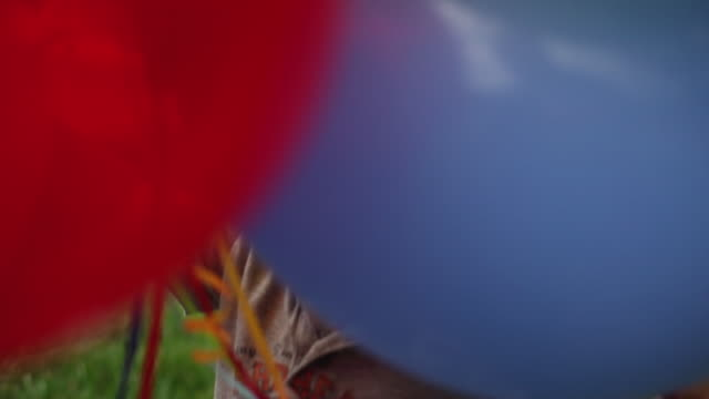 Handheld closeup shot of a cute toddler with balloons.