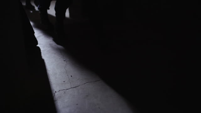 handheld dramatic shadows of a swat team on the floor of a warehouse. - aggressione video stock e b–roll