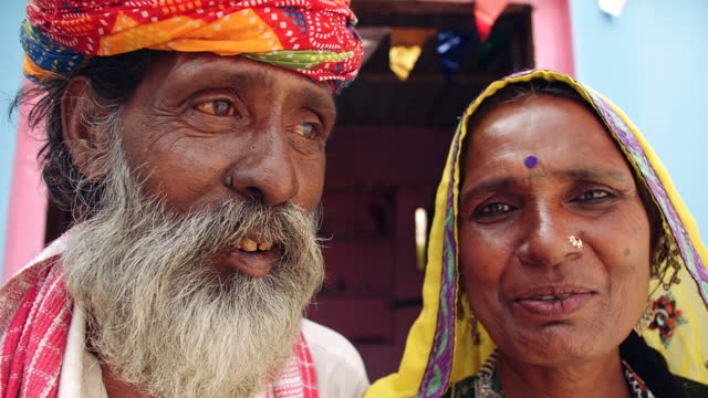 handheld extreme cu of an elder couple with colourful traditional costumes dress clothes speaking talking - human face video stock e b–roll