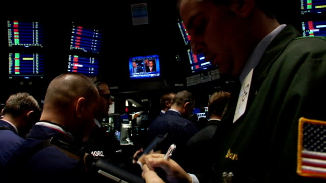 handheld eyelevel view walk past traders and monitors through trading floor of new york stock exchange new york city - bull market stock videos & royalty-free footage
