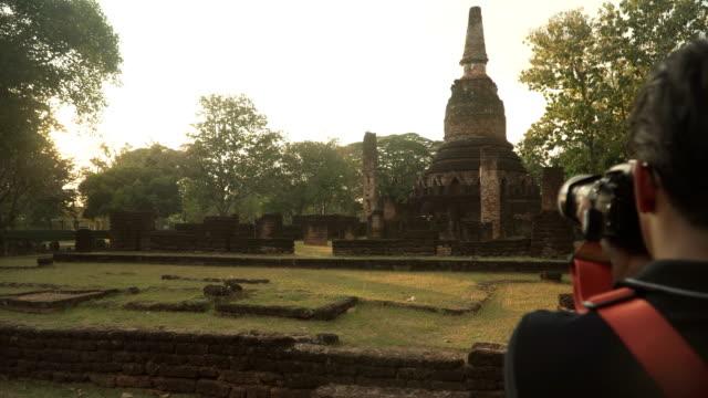 stockvideo's en b-roll-footage met handheld agenda wordt weergegeven om te achteraanzicht: jonge reiziger is het nemen van de foto van de ruïnes in kamphaengphet - menselijke rug