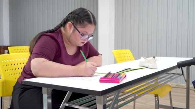 vídeos de stock, filmes e b-roll de visão frontal: uma adolescente com síndrome de down concentrada, fazendo lição de casa ou tarefa na sala de aula com amigos deficientes na cadeira de rodas na escola. as meninas estão sentadas em uma mesa, escrevendo, desenhando arte em papel com láp - só uma adolescente menina