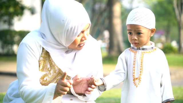 handheld front view: cheerful Muslim mother try to make her son no cry in public park in morning