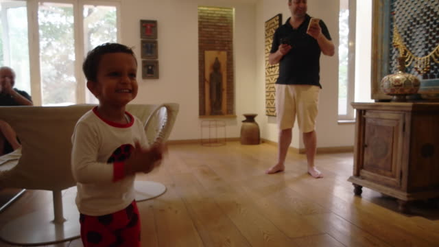 Handheld kid dancing and clapping after finishing his dancing with father and grand father