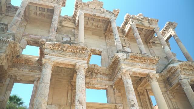 vidéos et rushes de vue de bas angle portatif : point de vue tandis que voyageur marchant dans l'arc architectural de vieille ruine et la porte de la bibliothèque de celsus, éphèse, kusadasi turquie. destination de voyage de l'arc de marbre et de la sculpture dans une  - monument
