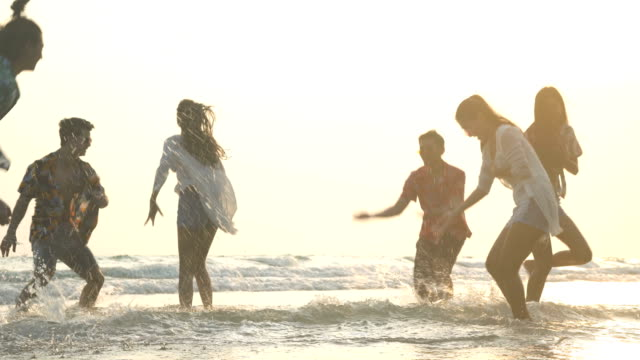handheld low angle view: six cheerful friends with exciting beach activities under sunset