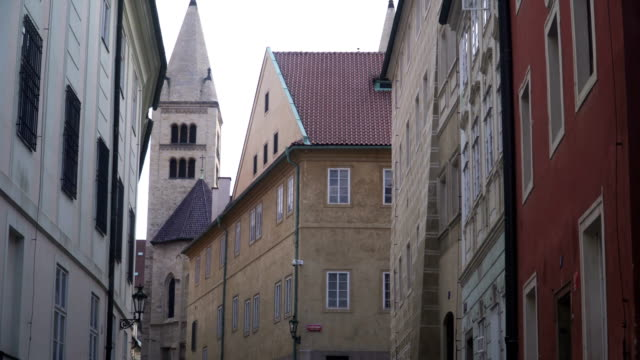 handheld low angle view: walking in local street to see old building and church in Prague city