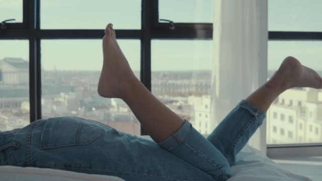 stockvideo's en b-roll-footage met handheld low section of woman moving legs while lying on bed at home - op de buik liggen