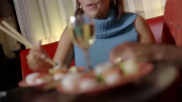 handheld medium shot couple eating sushi and laughing/ san antonio, texas - polo neck stock videos & royalty-free footage