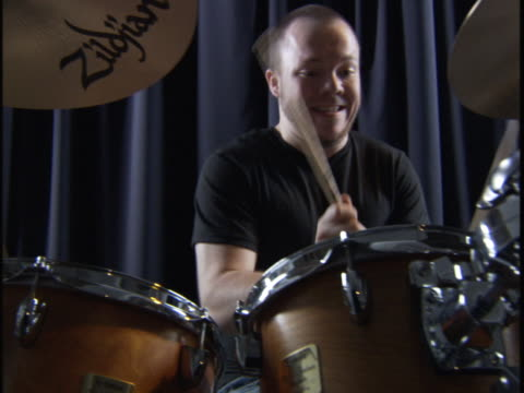 handheld medium shot of a young man as he plays the drums and smiles - one young man only stock videos & royalty-free footage