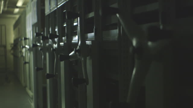 handheld medium shot of the handles of a grey mobile shelving system, uk. - e book stock videos & royalty-free footage