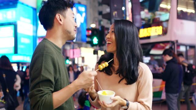 vidéos et rushes de slo mo photo de poche mid d'un jeune couple mangeant de la nourriture de rue à hong kong - rendez vous amoureux