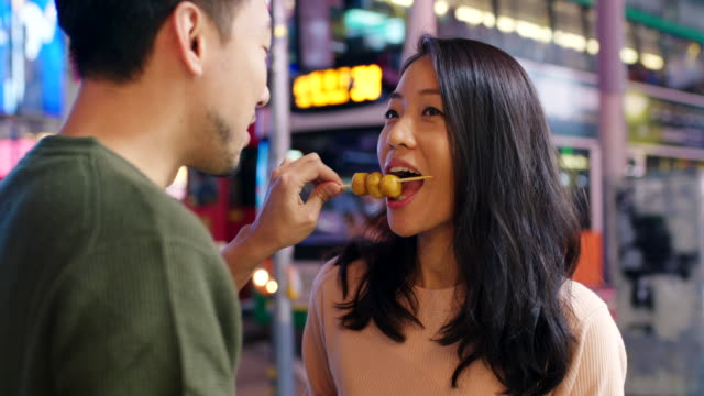 slo mo handheld mid shot of a young couple eating street food in hong kong - market stall stock videos & royalty-free footage
