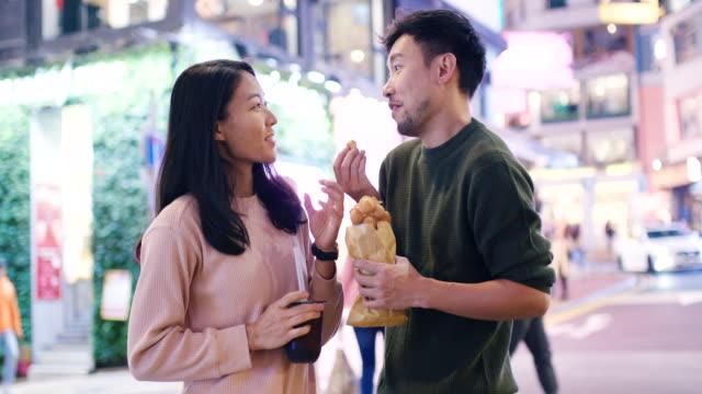 vidéos et rushes de slo mo photo de poche mid d'un jeune couple mangeant de la nourriture de rue traditionnelle à hong kong - jeune couple