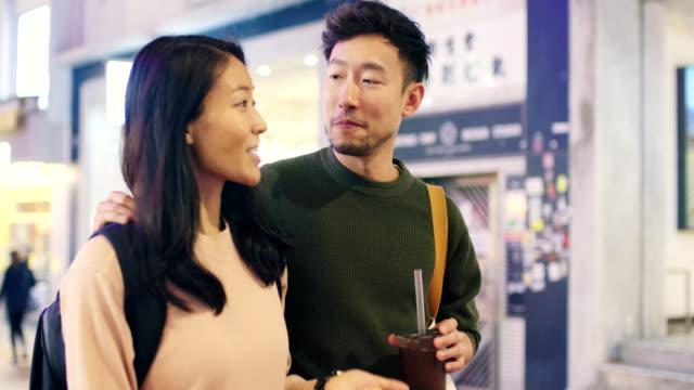slo mo handheld mid shot of a young couple walking through hong kong at night - hong kong stock videos & royalty-free footage