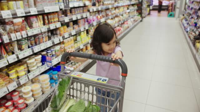 vídeos de stock, filmes e b-roll de handheld mid shot de uma jovem em um supermercado feliz empurrando um carrinho de compras - carrinho de compras