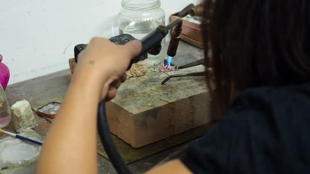 vidéos et rushes de handheld midsection of female artist making ring with blow torch on workbench in workshop - pince chirurgicale