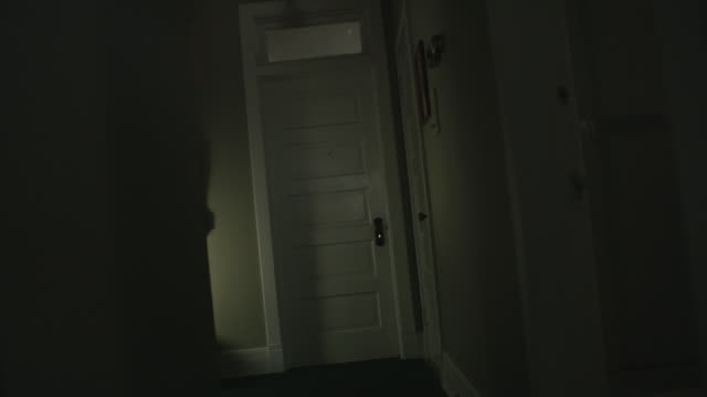 handheld pov moves down a dark, scary, vintage hallway toward a door, a mysterious shadow crosses the wall. - eingangshalle gebäudeteil stock-videos und b-roll-filmmaterial