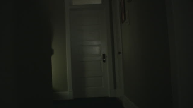 Handheld POV moves down a dark, scary, vintage hallway toward a door, a mysterious shadow crosses the wall.