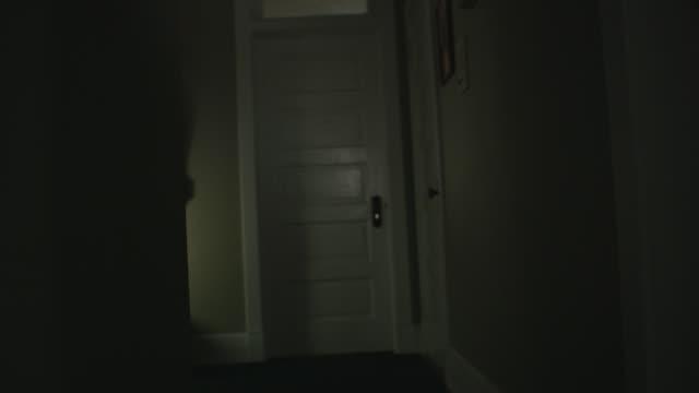 vídeos y material grabado en eventos de stock de handheld pov moves down a dark, scary, vintage hallway toward a door, a mysterious shadow crosses the wall. - pasillo de entrada