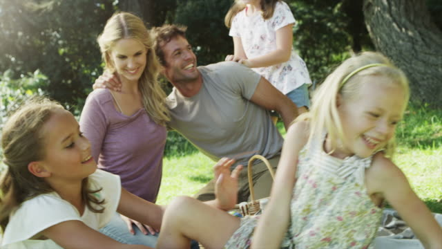 MS handheld of family having fun at picnic