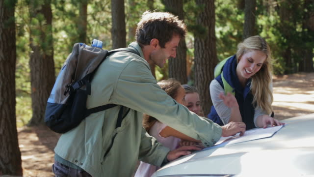 MS handheld of family looking at map in forest
