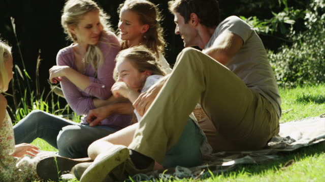 ms handheld of family messing about on grass - family with three children stock videos & royalty-free footage