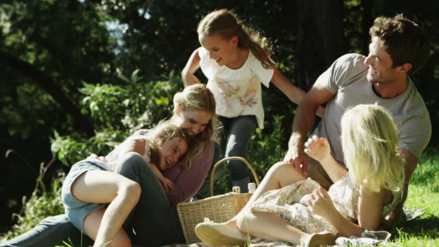 stockvideo's en b-roll-footage met ms handheld of family messing about on grass - picknick