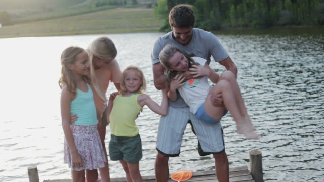 vidéos et rushes de ms handheld of family messing about on jetty by lake - jouer à la bagarre