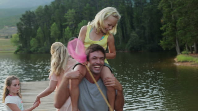 ms handheld of family on jetty by lake, daughter on dad's shoulders - daughter stock-videos und b-roll-filmmaterial