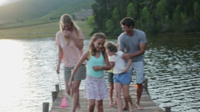 ms handheld of family walking along jetty by lake - family with three children stock videos & royalty-free footage