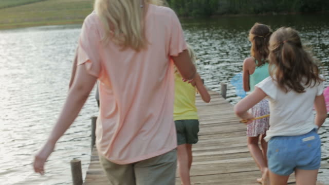 MS handheld of family walking along jetty by lake with fishing nets