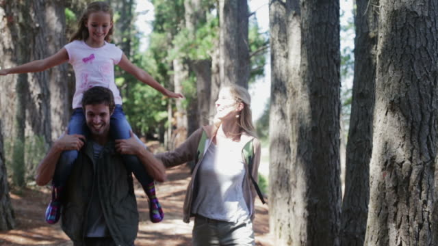 MS CU handheld of family walking in forest, daughter on Dad's shoulders