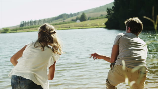 MS handheld of father and daughter skimming stones on lake