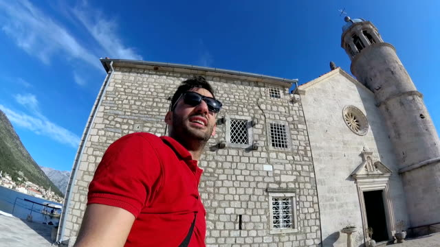 handheld of happy tourist man having online video chat using his smartphone near church - perast stock videos and b-roll footage