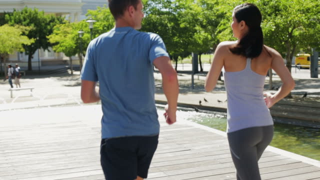 CU MS handheld of man and woman jogging in city