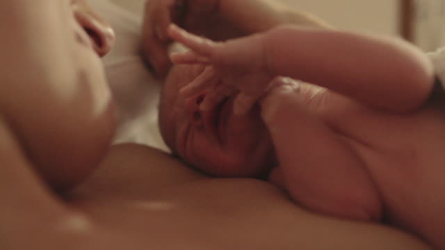 cu  handheld of mother smiling  and kissing newborn baby - 新生児点の映像素材/bロール