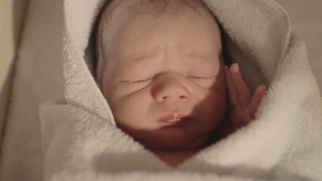ECU handheld of newborn baby opening his eyes