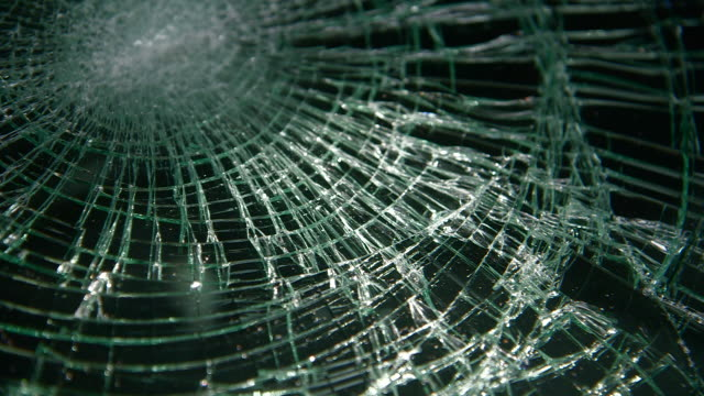 Handheld of the 'cobweb' pattern of a shattered windscreen, UK.
