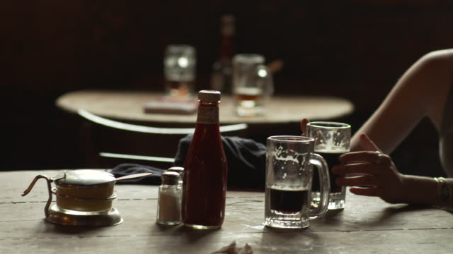 handheld pan from condiments and tankards of ale to a young woman and man drinking and chatting mcsorley's old ale house manhattan new york city usa... - condiments stock videos and b-roll footage