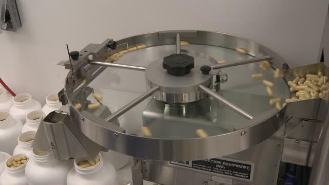 handheld pan shot of a capsule sorting machine. - haarnetz stock-videos und b-roll-filmmaterial