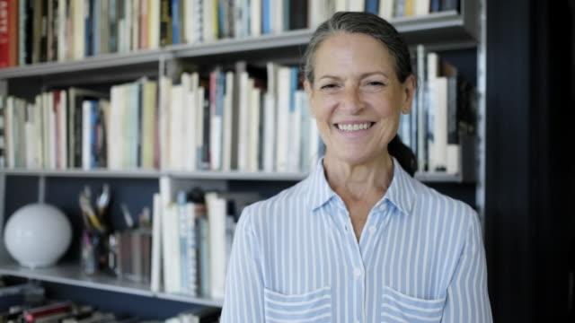 vídeos de stock e filmes b-roll de handheld portrait of a mature woman in an office. - 60 64 anos